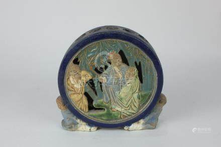 A Chinese pottery incense burner, the pierced design depicting sages, of circular form, supported by