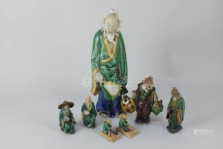 A collection of seven various Chinese glazed pottery figures to include a model of a deity