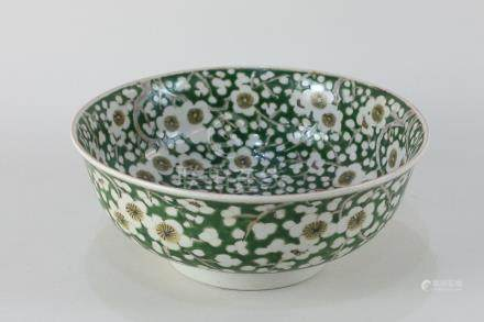 A Chinese porcelain bowl decorated with prunus blossom on green ground, character marks to base,