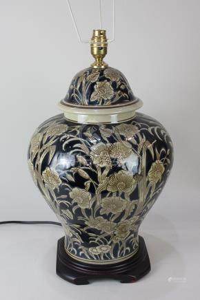 A Chinese porcelain baluster table lamp decorated with pale brown flowers on dark blue ground, on