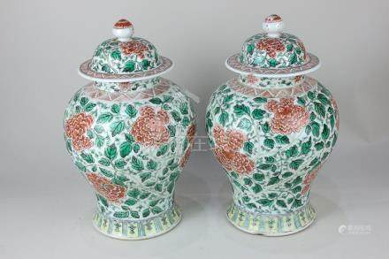 A pair of Chinese porcelain famille verte vases and covers decorated with flowers and foliage on