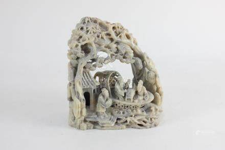 A Chinese carved hardstone ornament of a scene of figures in a boat within a surround of trees and