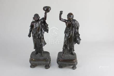 A pair of Japanese bronze standing figures, each with one arm held aloft, on rectangular base with