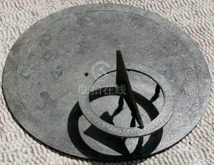 A Persian / Islamic large circular bronze sun dial engraved with figures, roundels and foliate