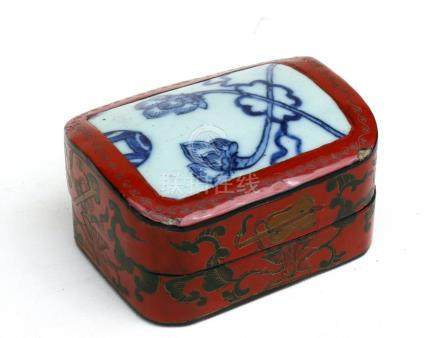 A Chinese lacquer box decorated with precious objects and foliate scrolls on a red ground with an