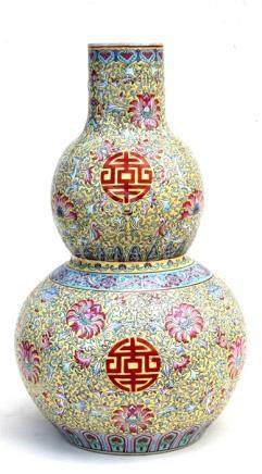 A Chinese famille rose double gourd vase decorated with foliate scrolls on a yellow ground, red seal