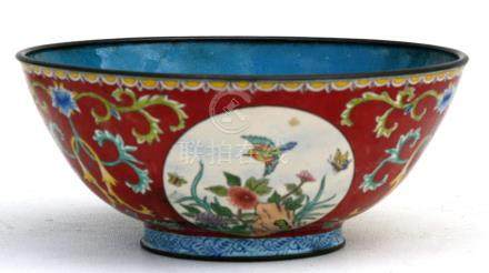 A Chinese enamel bowl decorated with birds, flowers and butterflies within roundels, on a red