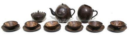 A coconut shell tea set comprising a teapot, sugar bowl, milk jug and cups & saucers.