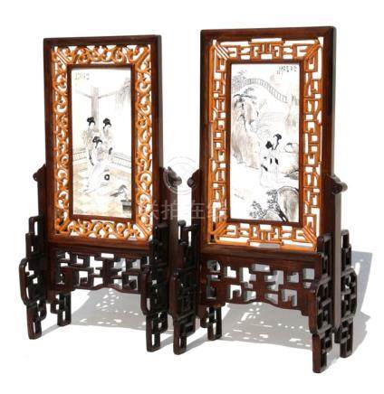 A pair of Chinese bone panels on hardwood stands, decorated with figures and calligraphy, 17cms (6.