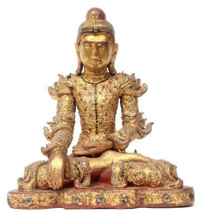 Wooden carving of a Buddha in typical pose, the wood with painted gilt decoration and inlaid glass