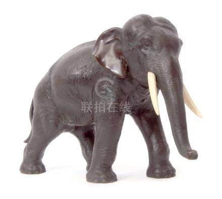 Japanese bronze model of an elephant, Meiji period, typically modelled with ivory tusks, 27cm long