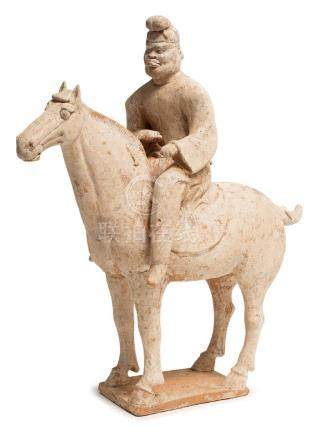 A POTTERY FIGURE OF HUMAN RIDING ON A HORSE