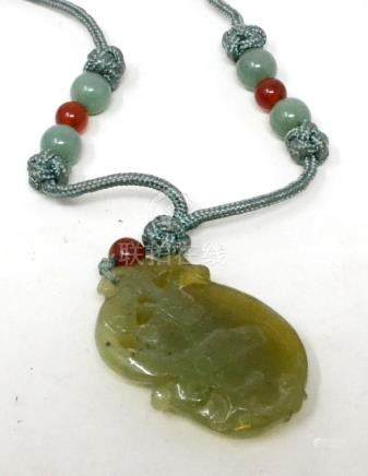 A Chinese carved and pierced jade pendant, in the form of a mythical animal on a fruit, the