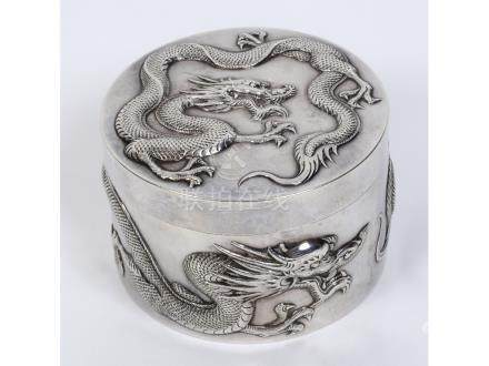 An early 20th century Chinese export silver coloured metal circular box and cover, embossed dragons,