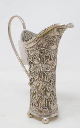 An early 20th century Chinese export silver coloured metal cream jug, initialled, embossed bamboo
