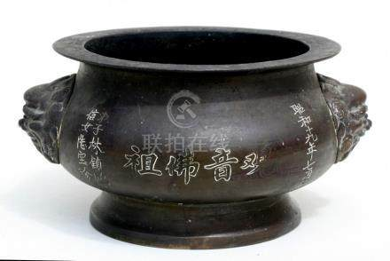 A Chinese bronze censer decorated with calligraphy and having two mask handles, 23cms (9ins)
