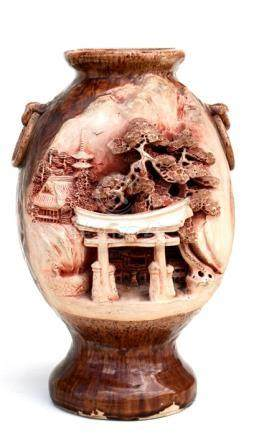 A Japanese pottery vase decorated with a temple, square seal mark to underside, 22cms (8.5ins)