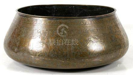 A large brass bowl decorated with a continual figural Egyptian scene, 43cms (17ins) diameter.