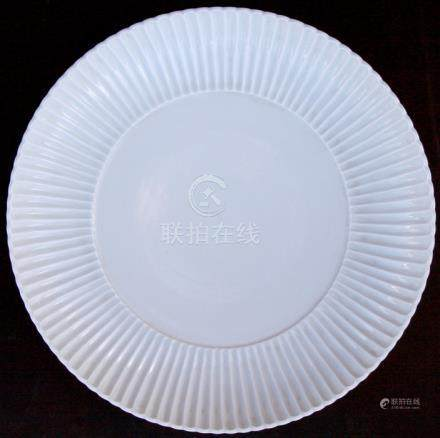 A large Chinese white glazed charger with ribbed border, blue Qianlong mark to base, 35cms (13.