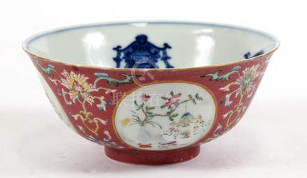 A Chinese famille rose bowl decorated with precious objects within roundels on a pink sgraffito