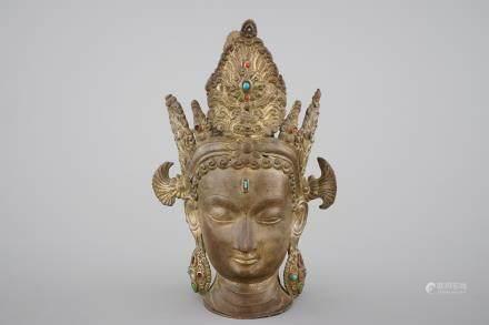 A tall gilt bronze head of a Boddhisatva with semi-precious stones, Tibet, 17/18th C.