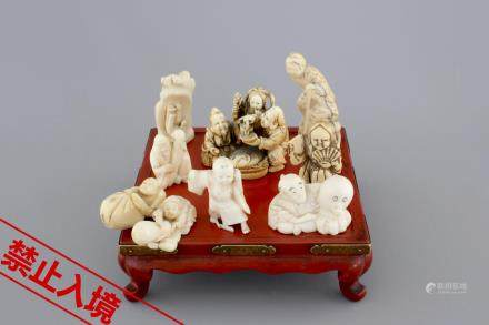 A set of 9 small Japanese ivory carvings, incl. netsuke, on a small red lacquer table, 19th/early 20th C.