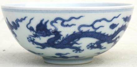 A Chinese blue & white bowl decorated with dragons amongst clouds with blue seal mark to