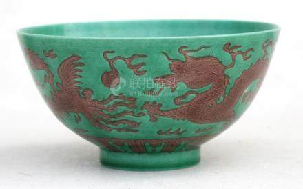 A Chinese bowl decorated with dragons and phoenix on a green ground with six-character mark to