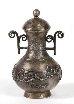 A Chinese white metal two handled vase and cover decorated in relief with birds in flowering prunus.