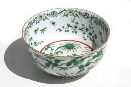 A Chinese famille verte bowl decorated with a central figure with a bird and deer, four-character