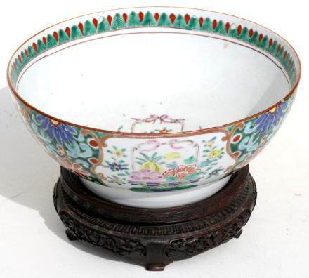 A 19th century Chinese famille rose bowl on a hardwood stand, 25cms (5.75ins) diameter.
