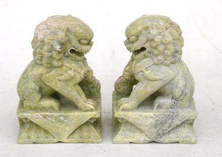A pair of Chinese pale green figured soapstone temple lions, 14cms (5.5ins) high.