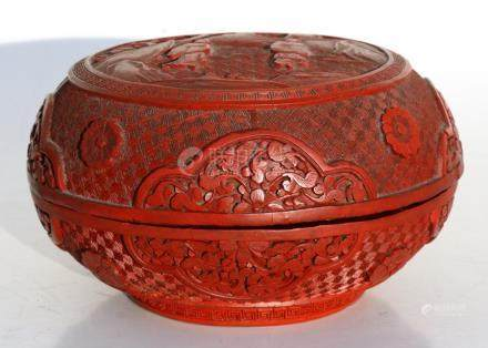 A Chinese cinnabar lacquer box & cover of compressed globular form, decorated with flowers and