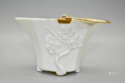 An interesting blanc-de-chine prunus libation cup with gilt
