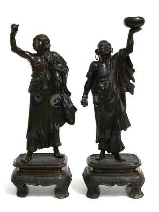 A pair of Japanese bronze figures on stands depicting robed monks, 33cms (13ins) high.