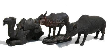 An Indian carved wooden figure of an ox; together with two similar carved wood figures, a camel