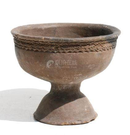 A Middle Eastern footed pottery bowl with incised decoration around the upper rim, 16cms (6.25ins)