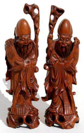 A pair of Chinese hardwood figures depicting Shoulau, 19cms (7.5ins) high.