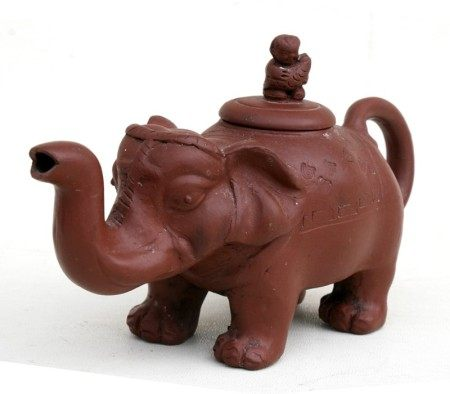 A Chinese Yixing pottery teapot in the form of an elephant with figural finial, 11.5cms (4.5ins)