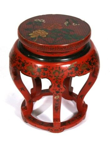 A Chinese lacquer stand decorated with flowers and scrolling foliage on a red ground, 48cms (
