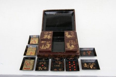 A 19th century Chinese Export lacquer games box decorated with gilded figures on a deep red
