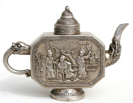 A Chinese white metal teapot decorated in relief with figures, four character mark to underside,