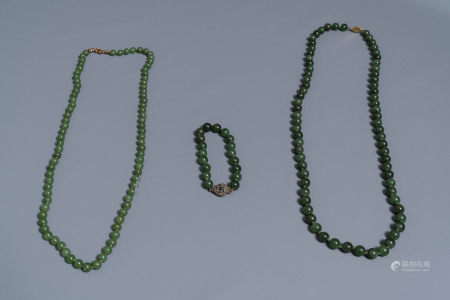 Two Chinese necklaces and a bracelet with spinach green jade beads, 20th C.