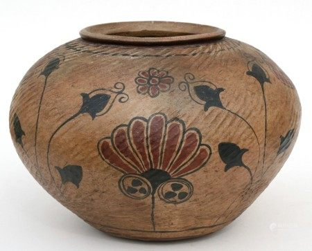 A North African terracotta pot decorated with flowers, 23cms (9ins) high.
