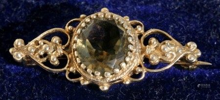 A Victorian yellow metal brooch set with a large oval pale green stone, 3.5cms (1.75ins) wide.