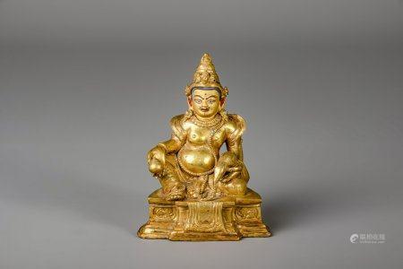 A Sino-Tibetan gilt bronze figure of Jambhala, 19th/20th C.