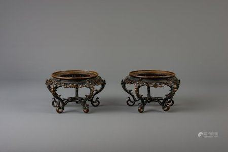 A pair of Chinese bronze open worked stands, Qianlong/Jiaqing