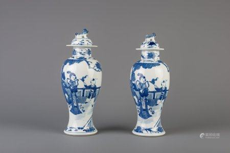 A pair of Chinese blue and white vases and covers with figures in a garden, Kangxi mark, 19th C.