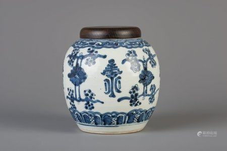 A Chinese blue and white ginger jar with floral design and a wooden cover, Kangxi
