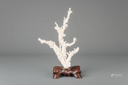 A Chinese carved white coral group depicting two ladies and a smiling boy on a wooden stand, Republic, 20th C.